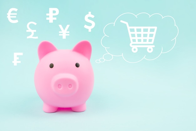 Pink piggy bank with digital hologram hologram world currencies and shopping cart in cloud thought above his head on blue background.