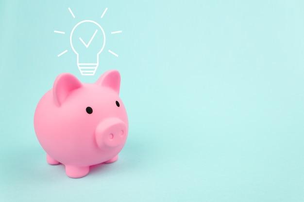 파란색 배경에 디지털 홀로그램 전구가 있는 분홍색 돼지 저금통. 비즈니스 혁신, 브레인스토밍, 영감 및 솔루션 개념.