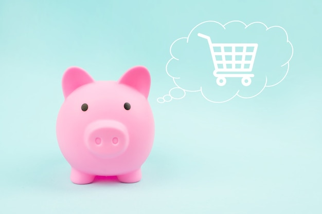 Pink piggy bank with digital hologram shopping cart in cloud thought above his head on blue background.