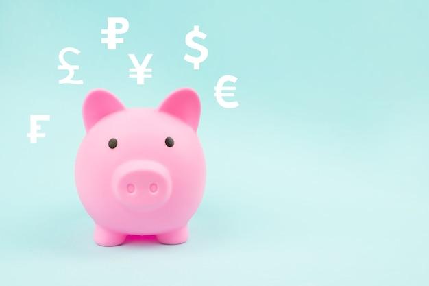 Pink piggy bank with digital hologram world currencies on blue background.