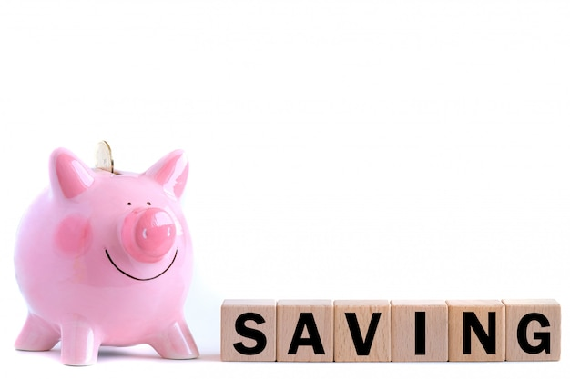Pink piggy bank with falling gold coin