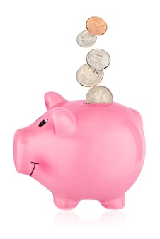 Pink piggy bank with falling us cent coins isolated on white