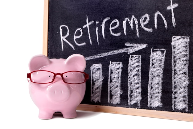 Pink piggy bank with glasses standing next to a blackboard with retirement savings message