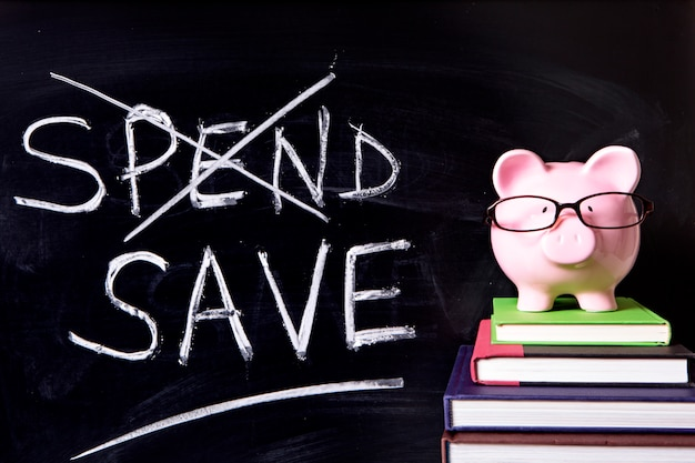 Pink piggy bank with glasses standing on books next to a blackboard