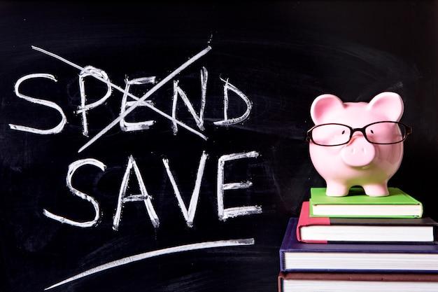Розовая копилка с очками стоит на книгах рядом с доской