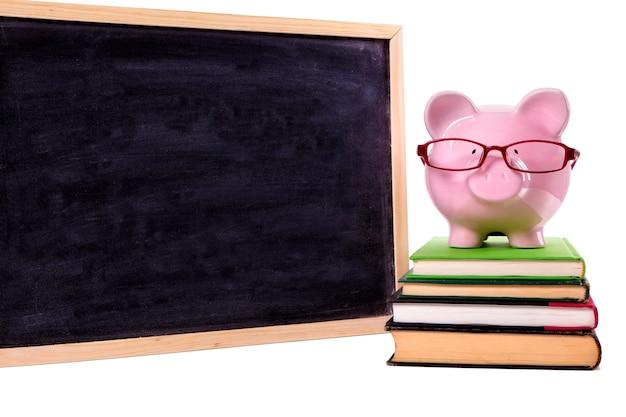 Розовая копилка с очками, стоящая на старых учебниках рядом с доской