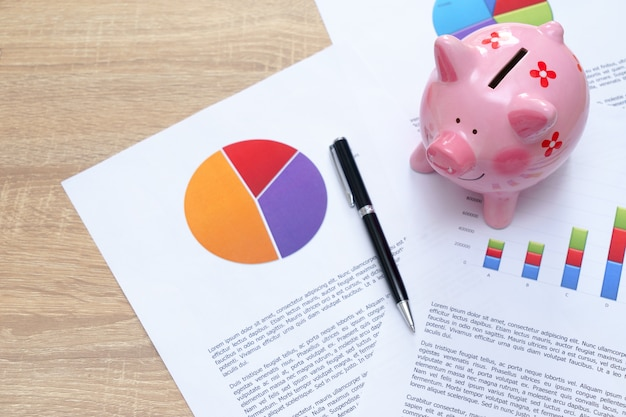 Pink piggy bank with graph and pen on wooden desk - growing interest rate concept.