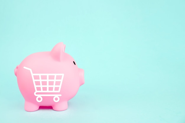 Pink piggy bank with mini shopping cart on blue background. saving money for sales of the year, black friday concept.