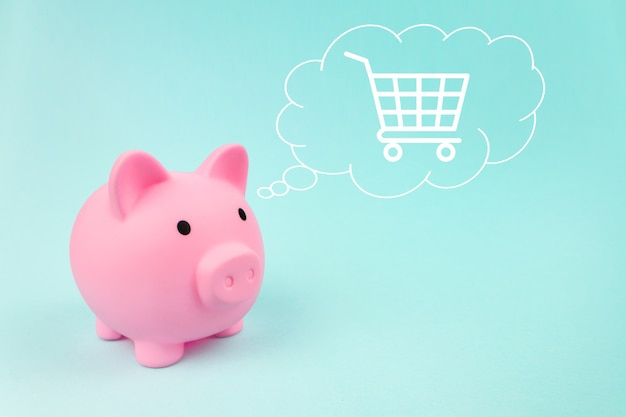Pink piggy bank with trolley digital hologram in cloud thought above his head on blue background.