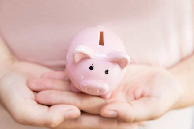 Pink piggy bank in womans hands. girl in pink holding piggy bank