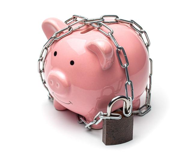 분홍색 돼지 저금통은 사슬로 싸여 있고 흰색 배경에 자물쇠로 잠겨 있습니다.