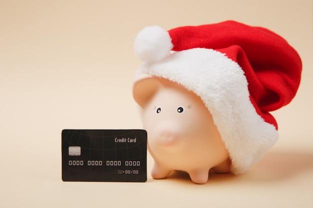 クリスマスの帽子、ベージュの背景に分離された黒のクレジットカードとピンクの貯金箱。お金の蓄積、投資、銀行またはビジネスサービス、富の概念。宇宙広告のモックアップをコピーします。