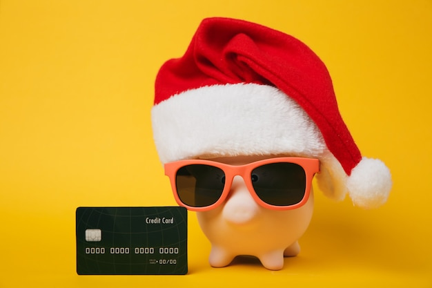 Pink piggy money bank with sunglasses christmas hat black credit card isolated on yellow wall background. money accumulation investment banking services wealth concept. copy space advertising mock up.
