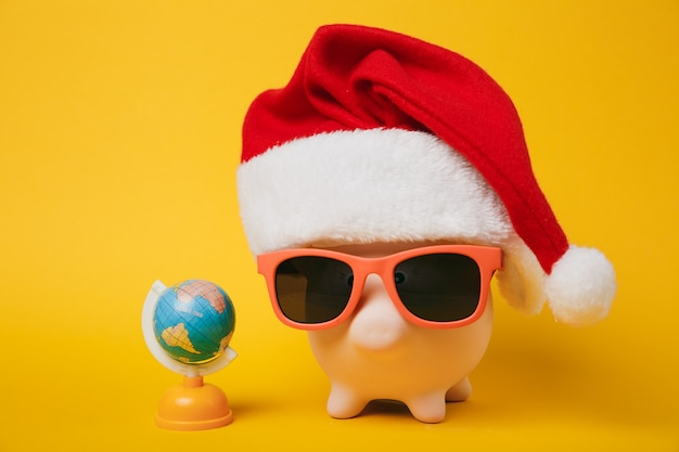 Pink piggy money bank with sunglasses christmas hat, toy earth world globe isolated on yellow background. money accumulation investment banking services wealth concept. copy space advertising mock up.