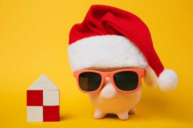 Pink piggy money bank with sunglasses christmas hat, toy wooden house isolated on yellow wall background. money accumulation investment banking services wealth concept. copy space advertising mock up.