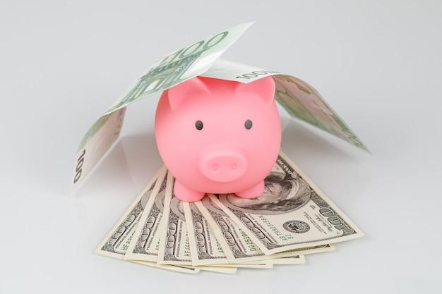 ドルとユーロの紙幣の山でピンクの貯金箱
