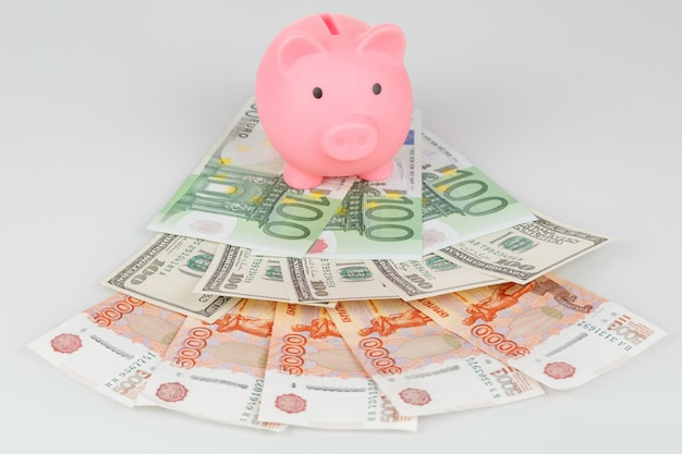 Pink piggy money box on pile of roubles, dollars and euro