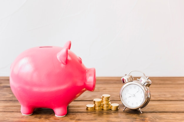 Pink piggybank near stacked coins and alarm clock