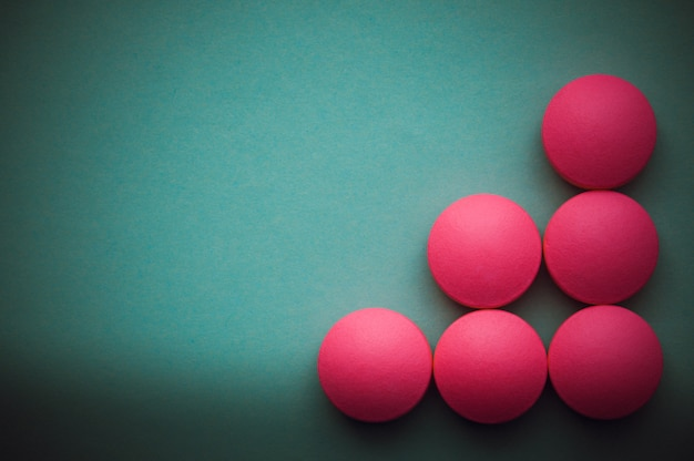 Pink pills laid out on a green background.