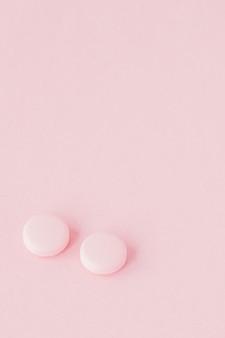 분홍색 배경에 분홍색 알 약, 복사 공간.