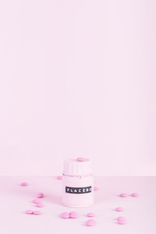 Pink pills surrounded with placebo closed bottle over pink background
