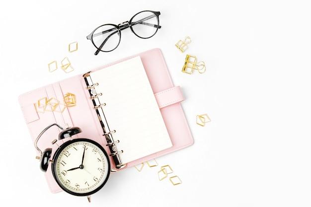 Розовый планировщик с будильником и бизнес-концепцией канцелярских принадлежностей. плоская планировка, вид сверху