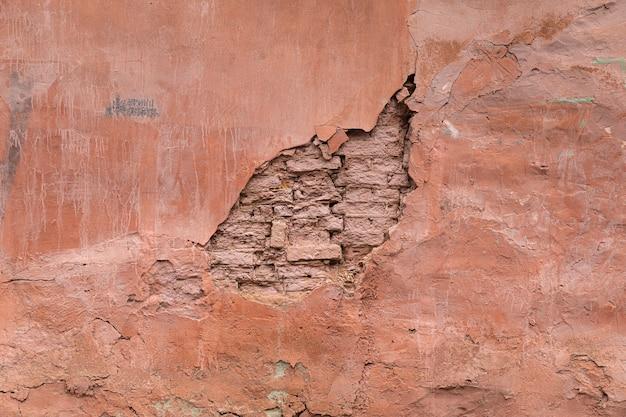 古い崩れかけた家の壁にピンクの漆喰。旧市街の背景とテクスチャ