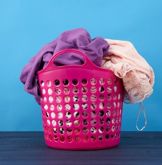 Pink plastic basket full of clothes and linen on a blue space