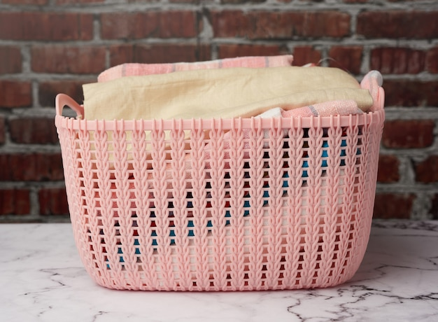 Pink plastic basket with folded washed linen
