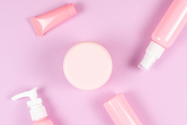 Pink plastic bottles for hygiene products, cosmetics, hygiene products on a pink wall. copy space.