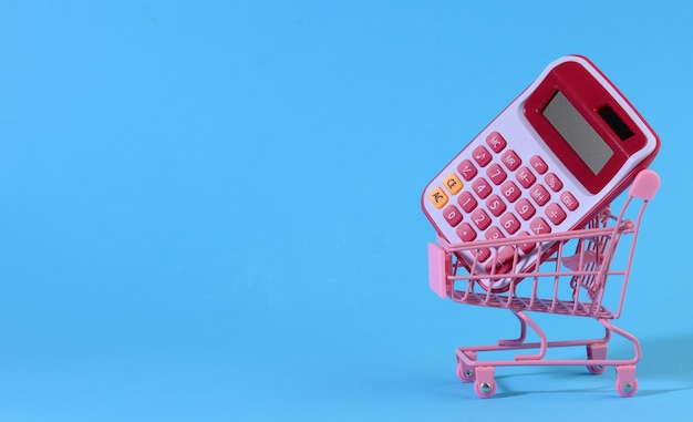 Pink plastic calculator in a miniature pink trolley on a blue surface. budget planning concept, savings counting, cost control, banner