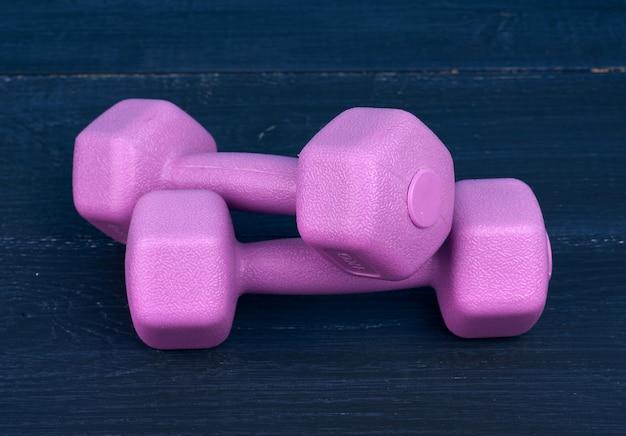 Розовые пластиковые гантели по одному килограмму на синем фоне