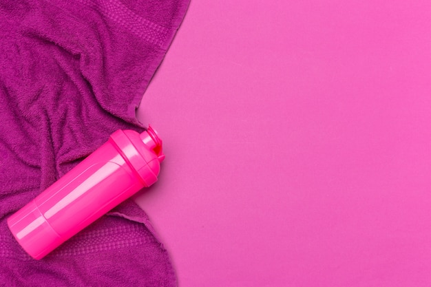 Pink plastic protein shaker cup on pink