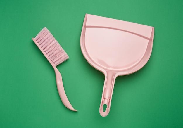 Розовый пластиковый совок и кисть на зеленой поверхности