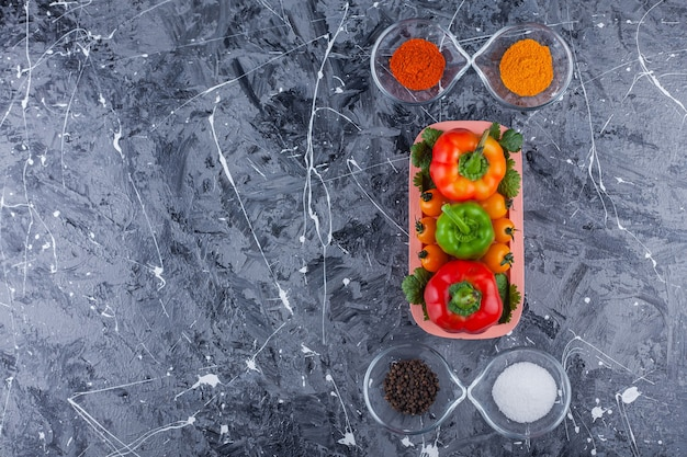 Pink plate of colorful peppers with various condiments on marble surface.