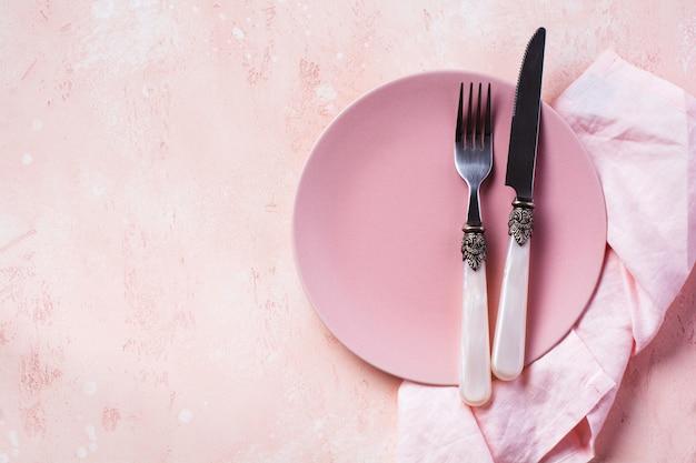 Розовая тарелка, столовые приборы и салфетка на каменном столе