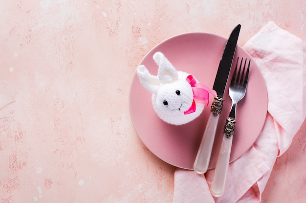 Pink plate, cutlery, napkin and white rabbit, symbol of easter napkin on stone table top view