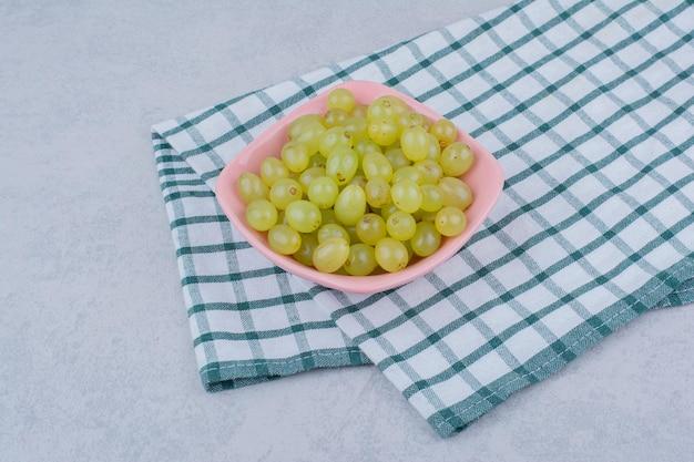 Un piatto rosa pieno di deliziose uve verdi. foto di alta qualità