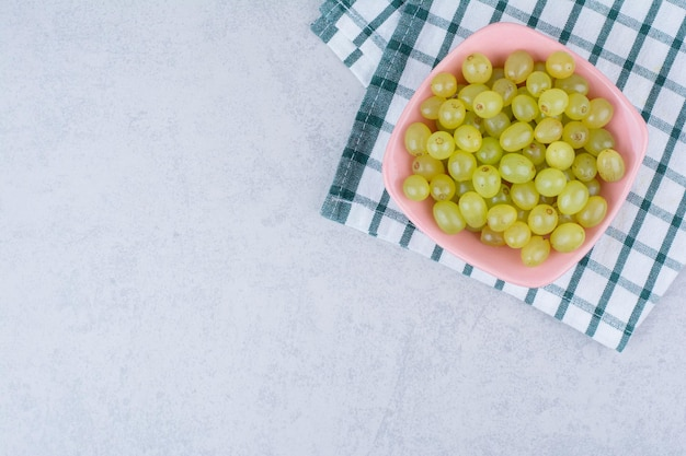 Un piatto rosa pieno di uva verde deliziosa.