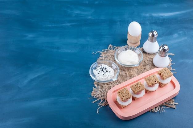 블루 표면에 흰색 치즈와 계란 썰어 빵의 핑크 플레이트.