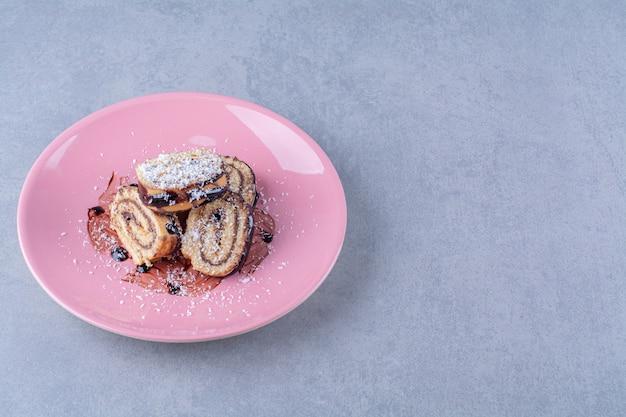Un piatto rosa di rotolo dolce a fette con sciroppo di cioccolato.