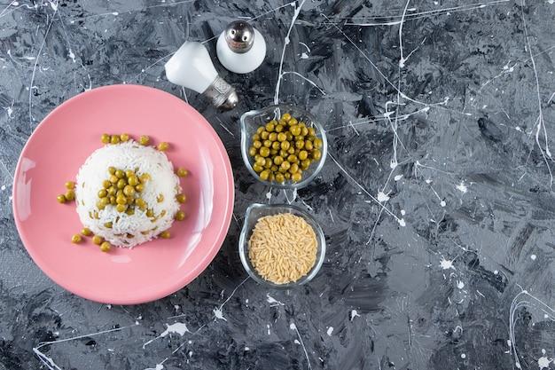 Розовая тарелка с отварным рисом и зеленым горошком на мраморном столе.