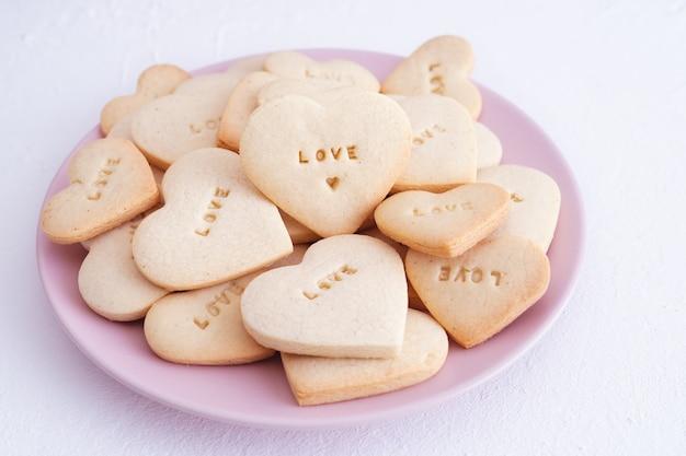 Розовая тарелка с печеньем в форме сердца и выгравированным словом love. концепция дня святого валентина и любовь.