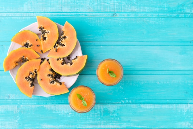 Pink plate with papaya slices on blue wooden background. copy space. top view.