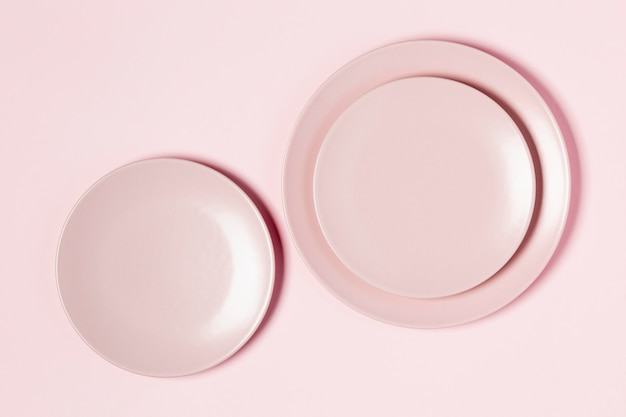 Pink plates arrangement on pink background