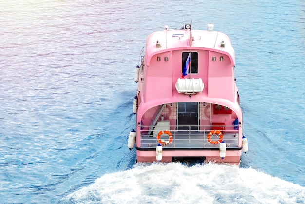 川沿いのピンクのプレジャーボート。コピースペース