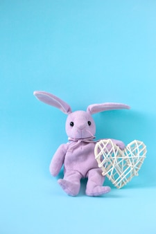 Pink plush hare sits on blue background and holds white heart, vertical orientation. valentine's day card