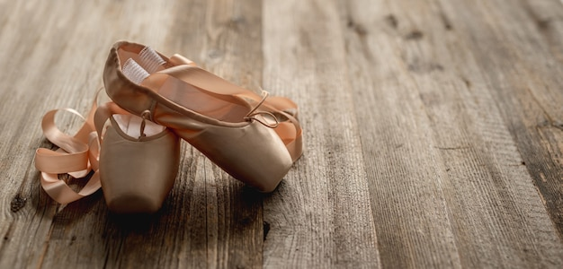 Pink pointe shoes with ribbons on wooden background, top view