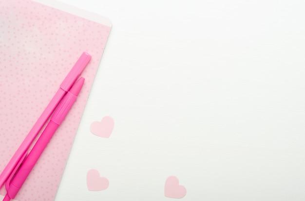 ピンクの水玉ノートとペン、白い木製の背景にハートをカットしました。スクールデスクの女の子。コピースペース、平面図、フラットレイアウト。