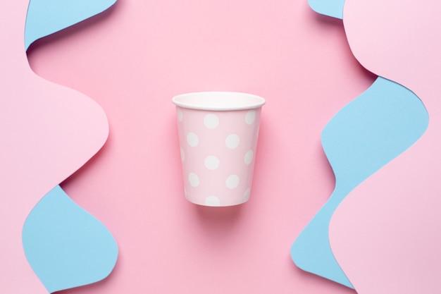 Розовый бумажный стаканчик в горошек и разные слои абстрактной бумаги, розовые и синие волны на пастельном виде сверху